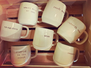 a collection of pottery mugs with customized text