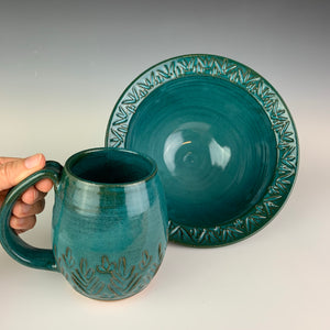 a carved rim bowl and matching carved mug, both in Teal glaze. made of stoneware