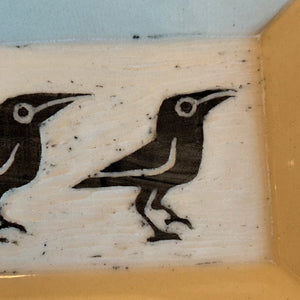 close up photo of crow platter with texture of carving showing through glaze.