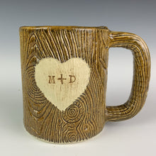 Load image into Gallery viewer, Large  custom coffee mug with lumberjack,woodgrain pattern impressed and carved in for texture you can feel. the mug has a heart carved into it with initials, like lovers would carve into a tree