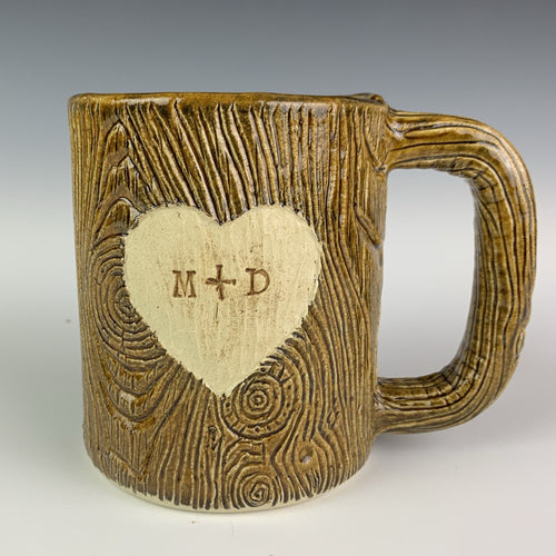 Large  custom coffee mug with lumberjack,woodgrain pattern impressed and carved in for texture you can feel. the mug has a heart carved into it with initials, like lovers would carve into a tree