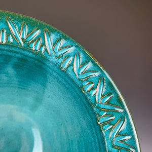 close up detail of the carved rim of a bowl. the red clay shows through the teal glaze at the edges of the carved lines.