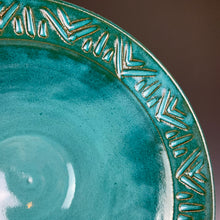 Load image into Gallery viewer, close up detail of the carved rim of a bowl. the red clay shows through the teal glaze at the edges of the carved lines.