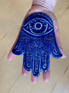 The artist holding a hand carved ceramic Hamsa in cobalt blue. The hamsa has an eye and a vine pattern carved into it.