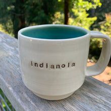 Load image into Gallery viewer, indianola mug, wheelthrown with the word indianola inset. white exterior, glossy turquoise interior