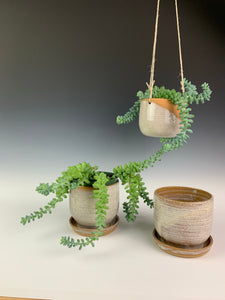 two pottery planters with drainage plates and one hanging planter