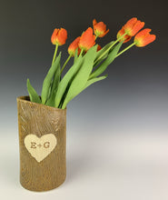 Load image into Gallery viewer, A pottery vase, with woodgrain texture and initials and a heart carved into the tree-like surface. shown with tulips
