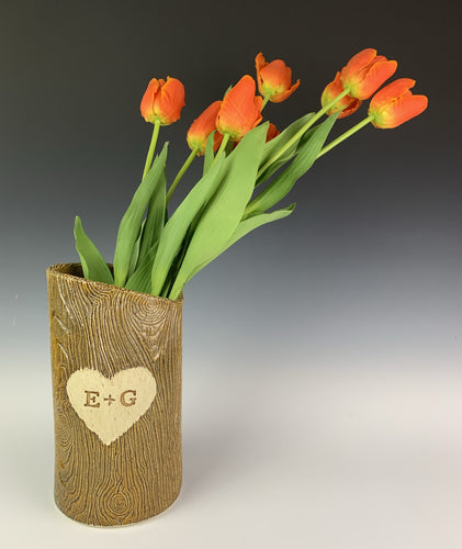 A pottery vase, with woodgrain texture and initials and a heart carved into the tree-like surface. shown with tulips