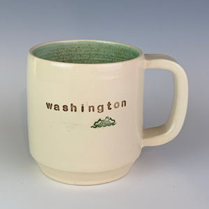 "Wheel thrown pottery mug with ""washington"" and an image of a ferry inset on the outside. white outside, green glaze interior"