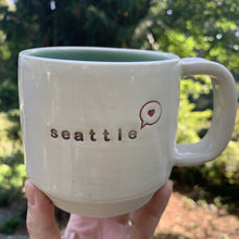 "Load image into Gallery viewer, seattle ""love"" mug, wheelthrown with heart in speech bubble image and the word seattle inset. white exterior, glossy turquoise interior"