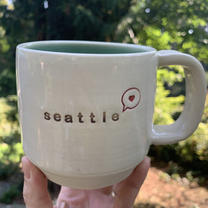 "seattle ""love"" mug, wheelthrown with heart in speech bubble image and the word seattle inset. white exterior, glossy turquoise interior"