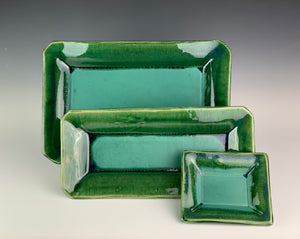 collection of serving trays in emerald city green