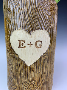close up detail texture shot of a woodgrain, lumberjack vase. the vase has a heart and initials carved into the wood-like surface