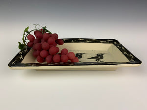 pottery crow platter with grapes. platter is sgraffito carved with crow pattern and crow footprint pattern. shown with grapes