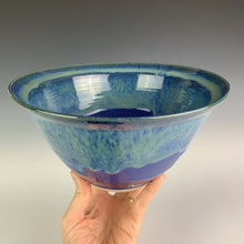 Load image into Gallery viewer, the artist holding a large wheel thrown pottery bowl, glazed in blue with turquoise green swirls melting from the rim.