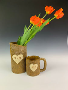 customized vase and mug shown together. pottery textured to look and feel like woodgrain, carved with initials and heart.