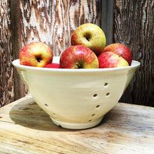 Load image into Gallery viewer, large pottery colander in pure white glaze, shown full of apples, rustic wood background