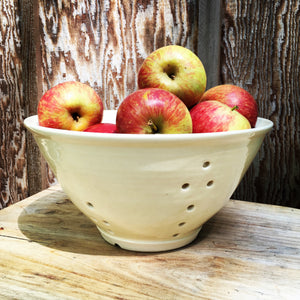 large pottery colander in pure white glaze, shown full of apples, rustic wood background