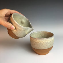 Load image into Gallery viewer, wheel thrown pottery cream and sugar set, shown here as the artist demonstrates pouring. red clay, white speckled glaze