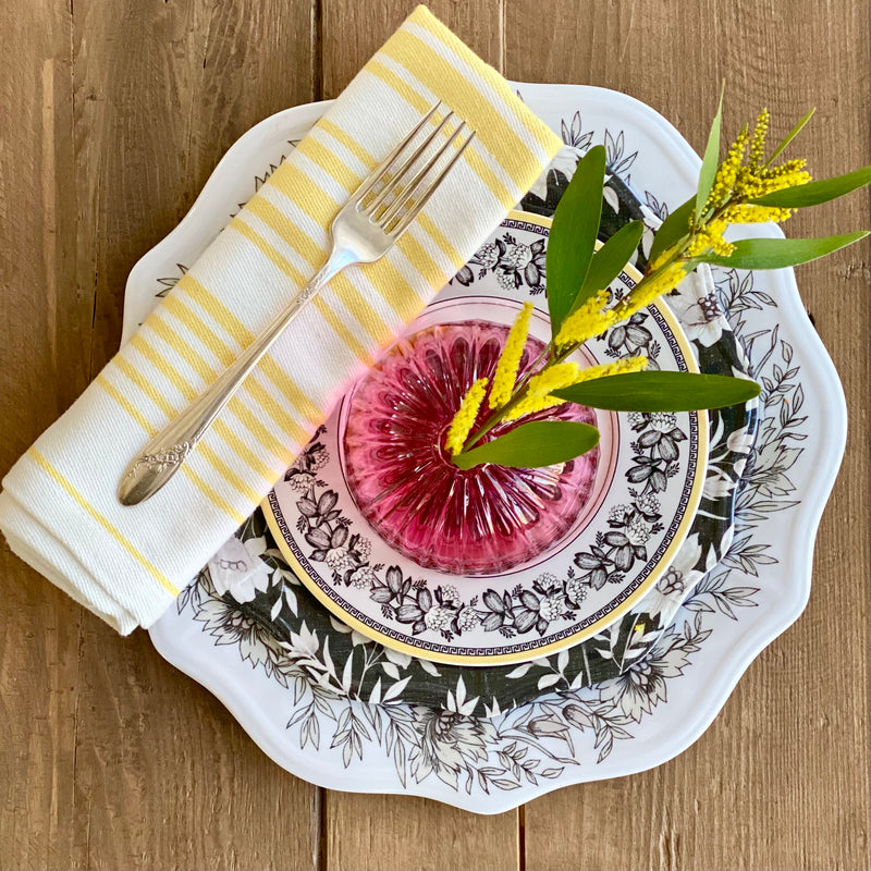 Beautiful place setting featuring the Hampton Gardens white floral melamine dinner plate, black and white floral melamine salad plate, a china dessert plate, and a pink glass vase on top with yellow acacia stem. Accented with yellow and white striped napkin.