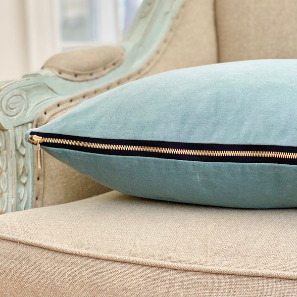 Soft blue velvet pillow with exposed zipper and pull rests on a vintage inspired armchair.