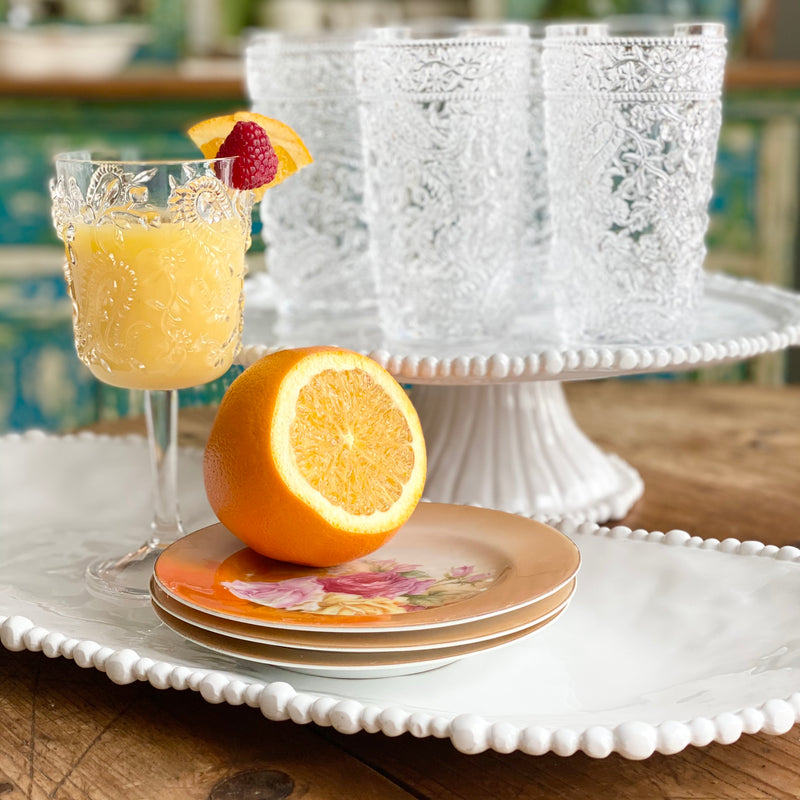 Beatriz Ball oval white melamine tray holding a cocktail and dessert plates and a white melamine Beatriz Ball cake pedestal holding glassware.