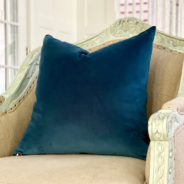 Deep water blue velvet square pillow rests atop a vintage-inspired armchair.