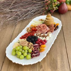 Large oval white melamine tray with elegant pearl edge by Beatriz Ball, showcasing an array of charcuterie.