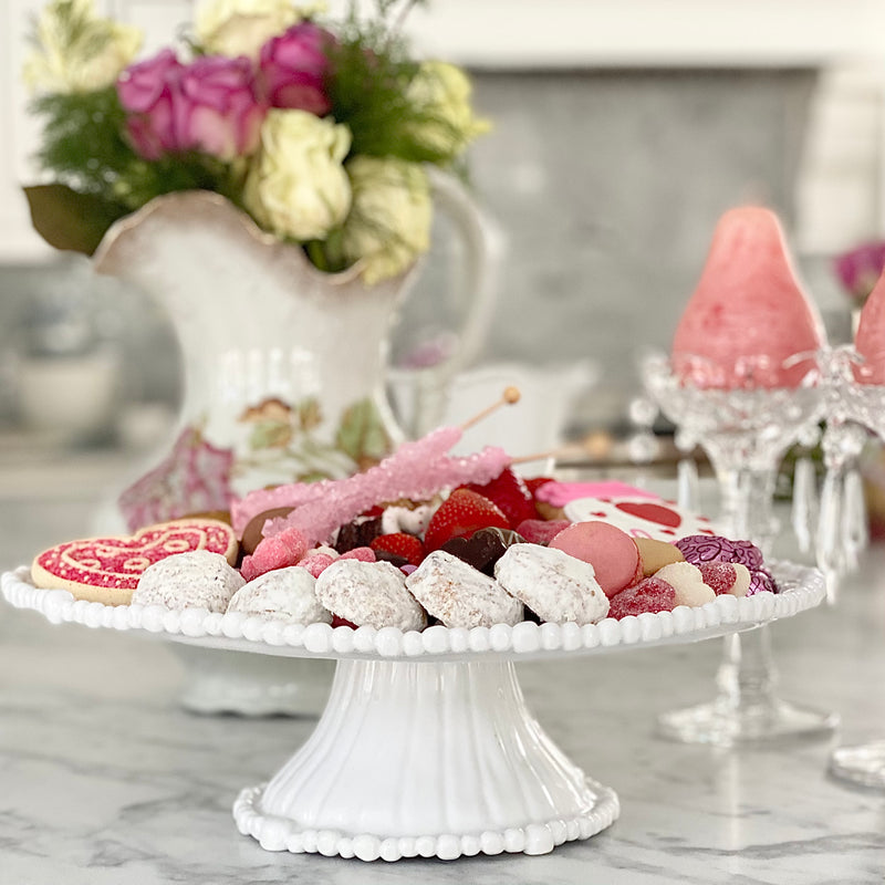 Pretty Beatriz Ball white melamine pedestal cake plate with cookies and fruit on top.