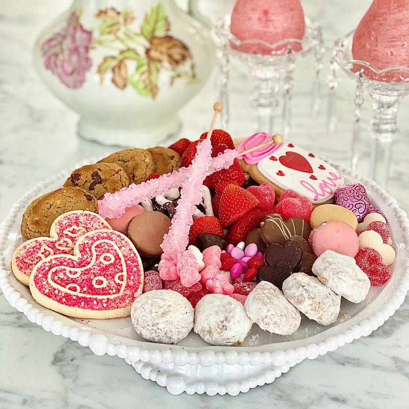 Beautiful white luxury melamine cake platter with cookies, candy and fruit on top, from the Alegria Collection by Beatriz Ball. Crystal candlesticks in background.