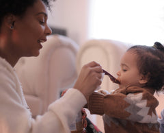 Woman Feeding A Child With a Spoon