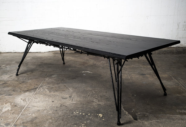 Photo of the Birdsnest Table made out of an ebonized white ash top and blackened steel base that resembles the branches of a birdsnest.