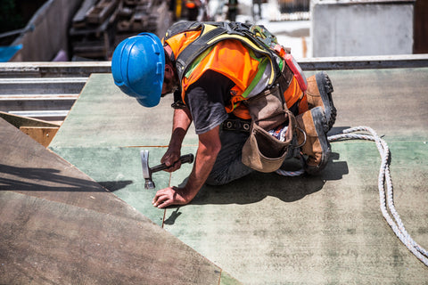 Construction worker in a safety vest hammering nails