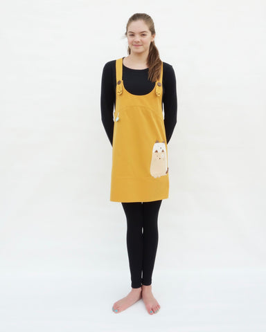 Woman wearing yellow, cat dress with cat appliqué, embroidery details, adjustable straps, in front view.