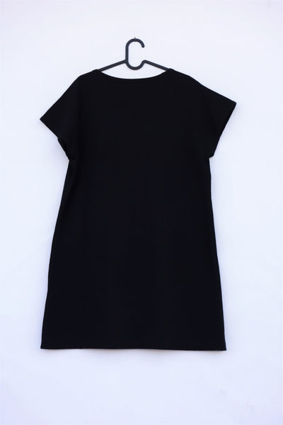 Woman's black, cat shift-dress with short sleeves, rounded neck opening, on hanger, in back view.