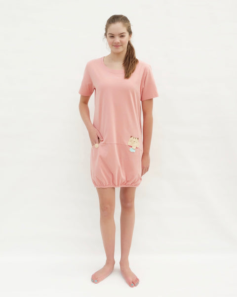 Woman wearing cat t-shirt dress in pink with cat appliqué, embroidery, front pockets, round neck opening, short sleeves, in front view.