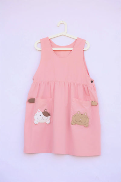 pink sleeveless cat dress with cats and cat tails on pockets, buttons on each side