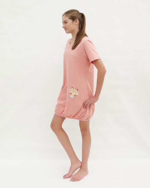 Woman wearing cat t-shirt dress in pink with cat appliqué, embroidery, front pockets, round neck opening, short sleeves, in side full-body view.