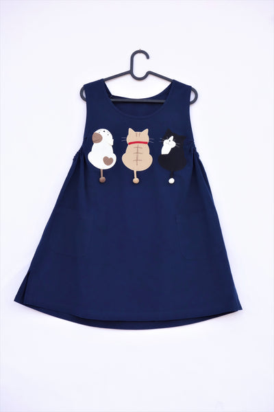 A cat-themed, cotton, dark-blue navy shirt/mini A-line dress/top/tunic on a hanger with three appliqué cats on the front