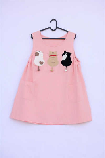 A cat-themed, cotton, pink shirt/mini A-line dress/top/tunic on a hanger with three appliqué cats on the front