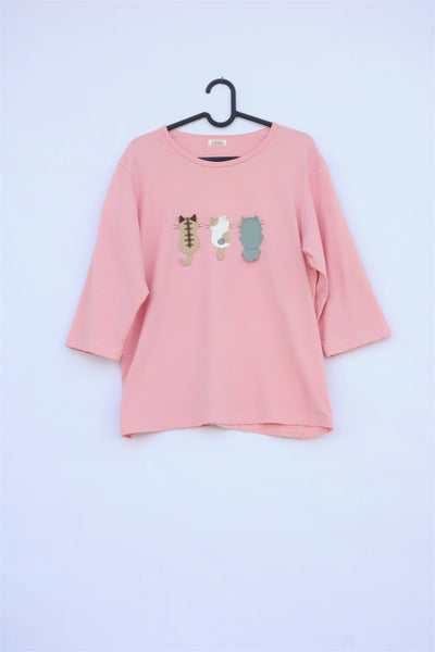 A pink cotton cat-themed shirt on a hanger with 3 appliqué cats on the front, their backs facing. The top has a rounded neck and three quarter sleeves.