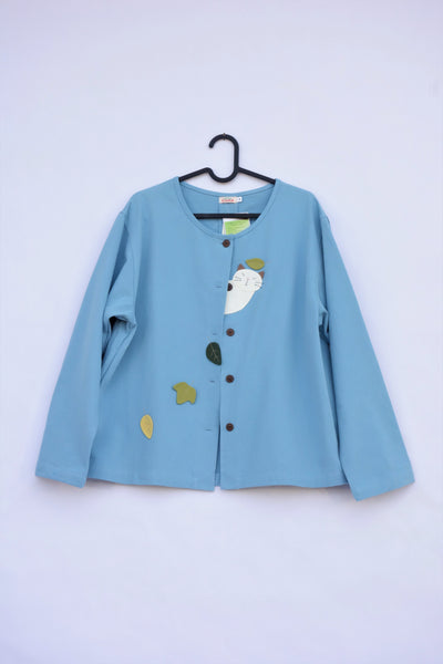 A blue women's boxy-fit cotton cat jacket on a hanger with appliqué cat and leaves on the front. There are buttons on the jacket.
