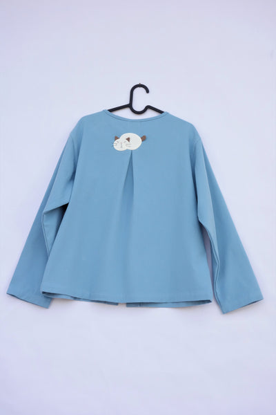 A blue womens' boxy-fit cotton cat jacket on a hanger with an appliqué cat sleeping on the back. There is a pleat on the back of the jacket.