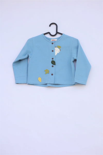 A blue girls' boxy-fit cotton cat jacket on a hanger with appliqué cat and leaves on the front. There are buttons on the jacket.