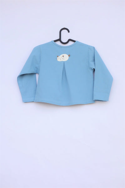 A blue girls' boxy-fit cotton cat jacket on a hanger with an appliqué cat sleeping on the back. There is a pleat on the back of the jacket.