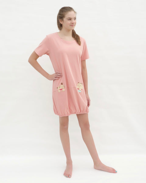 Woman wearing cat t-shirt dress in pink with cat appliqué, embroidery, front pockets, round neck opening, short sleeves, in 3/4 front view.