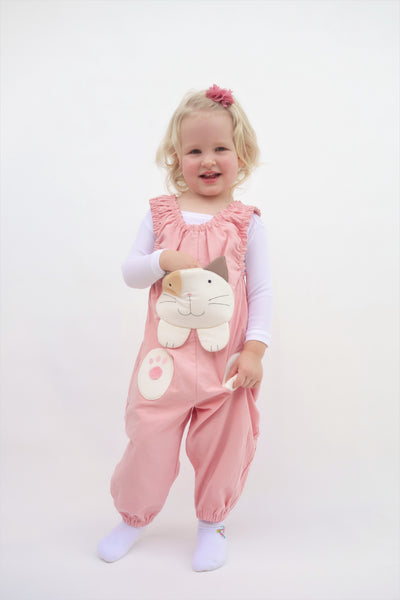 Girl with one hand tucked inside a pocket and a wearing pink, cat-themed jumper with large, soft cat face pocket and cat paws in the front, two little fish friends swim on the back, sewn appliqué, embroidery details and side pockets in front view.