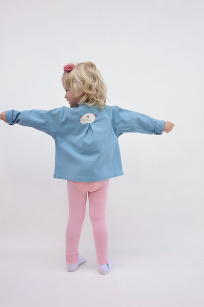 A girl is wearing a blue relaxed-fit cotton cat jacket with an appliqué sleeping cat on the back. Her arms are stretching out. There is a pleat on the back of the jacket.