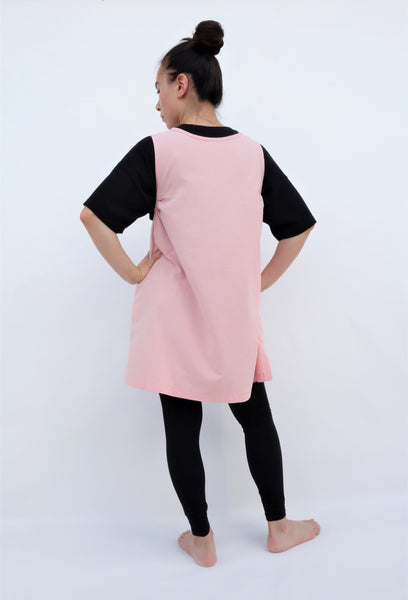 A woman standing and wearing a cat-themed, cotton, pink shirt/mini A-line dress/top/tunic, back view