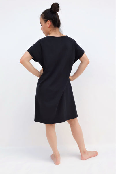 Woman wearing black, cat shift-dress with short sleeves, rounded neck opening in back view.